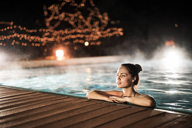 Woman spending a winter night in a heated swimming pool.
